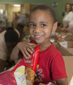 Child receiving food from a Florida homeless coalition